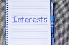 Los intereses escriben en el cuaderno Foto de archivo