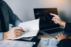 Los inversores están utilizando una pluma a escribir los datos para la compañía que está analizando las partes con los colegas en fotos de archivo libres de regalías
