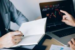 Los inversores est?n utilizando una pluma a escribir los datos para la compa??a que est? analizando las partes con los colegas en imágenes de archivo libres de regalías