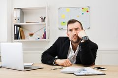 Los jóvenes aburrieron al hombre de negocios con el ordenador portátil en oficina blanca moderna fotografía de archivo
