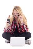 Los jóvenes asombraron a la mujer del blondie que se sentaba con el ordenador portátil y el pH móvil Imágenes de archivo libres de regalías
