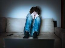 Los jóvenes asustados sirven están mirando horror o la novela de suspense en la TV fotografía de archivo