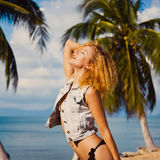 Los jóvenes broncean a la muchacha atractiva delgada del pelirrojo en fondo del cielo azul en el mar del verano Imagen de archivo libre de regalías