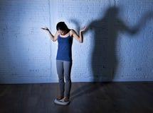 Los jóvenes caben y adelgazan a la mujer que comprueba el peso corporal en escala con la luz nerviosa grande de la sombra triste  Foto de archivo