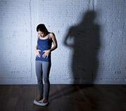 Los jóvenes caben y adelgazan a la mujer que comprueba el peso corporal en escala con la luz nerviosa grande de la sombra triste  Imagen de archivo libre de regalías