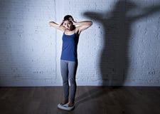 Los jóvenes caben y adelgazan a la mujer que comprueba el peso corporal en escala con la luz nerviosa grande de la sombra triste  Fotos de archivo libres de regalías