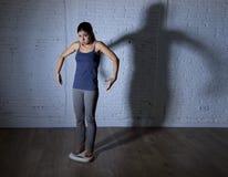Los jóvenes caben y adelgazan a la mujer que comprueba el peso corporal en escala con la luz nerviosa grande de la sombra triste  Foto de archivo libre de regalías