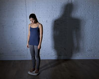 Los jóvenes caben y adelgazan a la mujer que comprueba el peso corporal en escala con la luz nerviosa grande de la sombra triste  Imagenes de archivo