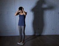 Los jóvenes caben y adelgazan a la mujer que comprueba el peso corporal en escala con la luz nerviosa grande de la sombra triste  Fotografía de archivo libre de regalías