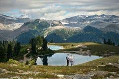 Los jóvenes casados juntan caminar en montañas cerca de los lagos y de los glaciares alpinos hermosos imagenes de archivo