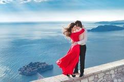 Los jóvenes casados juntan el abarcamiento Muchacha de la moda en vestido rojo con h Imagen de archivo libre de regalías