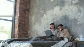 Los jóvenes casados juntan el trabajo en el ordenador portátil en cama almacen de video
