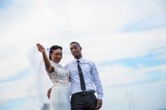 Los jóvenes casados juntan la presentación al aire libre con el cielo en fondo imagenes de archivo