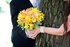 Los jóvenes casados juntan llevar a cabo las manos Fotografía de archivo libre de regalías