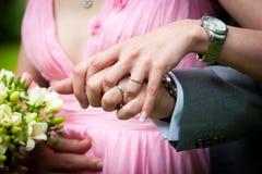 Los jóvenes casados juntan llevar a cabo las manos Foto de archivo libre de regalías
