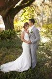 Los jóvenes casados se juntan en el jardín Foto de archivo libre de regalías
