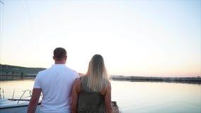Los jóvenes casados se juntan están dando un paseo en un embarcadero por la tarde, visión trasera almacen de metraje de vídeo