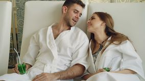 Los jóvenes casados se juntan están relajando sentarse en salón moderno del balneario con los vidrios de cóctel, la charla y besa almacen de metraje de vídeo