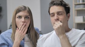 Los jóvenes chocados se juntan en el sofá que se pregunta en temor metrajes