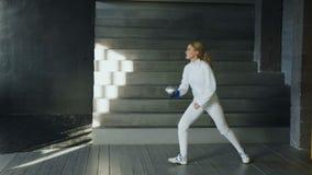Los jóvenes concentraron la práctica de la mujer del cercador que cercaba ejercicios y que entrenaba para la competencia de los J almacen de metraje de vídeo