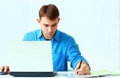 Los jóvenes concentraron notas de la escritura del hombre de negocios abajo con el ordenador portátil Foto de archivo libre de regalías