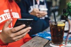 Los jóvenes conectaron con un teléfono y la consumición de un coque Imágenes de archivo libres de regalías