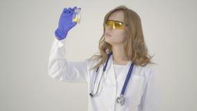 Los jóvenes cuidan - al trabajador médico de la mujer hermosa que sostiene el tarro de píldoras en el fondo blanco metrajes