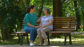Los jóvenes cuidan día soleado del gasto con la mujer mayor en parque almacen de metraje de vídeo