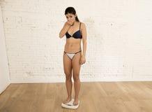 Los jóvenes cupieron la mujer delgada o a la muchacha adolescente que comprobaba el peso corporal en el hallazgo de la escala mis Foto de archivo libre de regalías