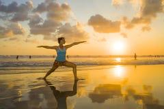 Los jóvenes cupieron y mujer atractiva del deporte en entrenamiento de la práctica de la yoga de la puesta del sol de la playa en fotografía de archivo