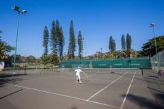 Los jóvenes de la acción del tenis escogen en corte Imagen de archivo libre de regalías