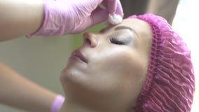 Los jóvenes de la cara durante reciben procedimiento de la belleza Cuide al paciente de limpiamiento de la cara de la piel del co almacen de video