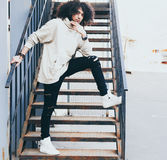 Los jóvenes de moda vistieron al hombre en un equipo fresco que presentaba en una escalera del metal Pelo del estilo del Afro Str Fotos de archivo