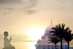 Los jóvenes de los musulmanes ruegan para la paz del koran de la lectura de dios en el Ea medio Foto de archivo libre de regalías