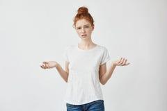 Los jóvenes descontentaron a la muchacha del pelirrojo que gesticulaba mirando la cámara Muchacha confusa que discute con un novi Foto de archivo libre de regalías