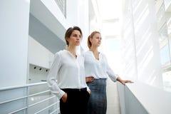 Los jóvenes dos trabajadores profesionales de sexo femenino se vistieron en la ropa corporativa que se colocaba en interior moder Fotografía de archivo libre de regalías