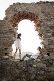 Los jóvenes en amor juntan sentarse dentro de arcada del ladrillo de la ruina vieja Imagenes de archivo