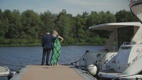 Los jóvenes en pares del amor se colocan en el embarcadero y disfrutan de la hermosa vista del río almacen de video