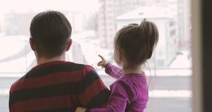 Los jóvenes engendran los controles una pequeña hija en sus brazos y puntos una mano a la distancia almacen de metraje de vídeo