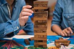 Los jóvenes están jugando al juego de madera del jenga Fotografía de archivo