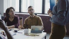 Los jóvenes felices combinan el trabajo en la oficina del desván, discutiendo proyecto Líder de sexo femenino que da el grupo de  almacen de video