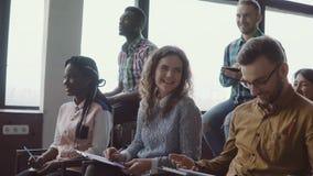Los jóvenes felices combinan sentarse en la oficina del desván en el seminario del negocio El grupo de personas de la raza mixta  almacen de metraje de vídeo
