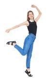 Los jóvenes felices forman a la muchacha en el salto de los vaqueros aislada Imagen de archivo libre de regalías