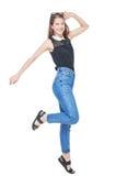Los jóvenes felices forman a la muchacha en el salto de los vaqueros aislada Imagen de archivo