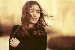 Los jóvenes felices forman a la muchacha que camina en el viento Imagen de archivo libre de regalías