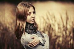 Los jóvenes felices forman a la muchacha que camina por el lago al aire libre Imagen de archivo