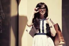 Los jóvenes felices forman a la mujer en gafas de sol con los panieres fotografía de archivo