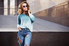 Los jóvenes felices forman a la mujer en gafas de sol en la calle de la ciudad Fotografía de archivo libre de regalías