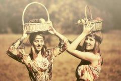 Los jóvenes felices forman a muchachas con caminar de la cesta de fruta al aire libre Imagen de archivo libre de regalías