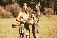 Los jóvenes felices forman a muchachas con caminar de la cesta de fruta al aire libre Foto de archivo libre de regalías